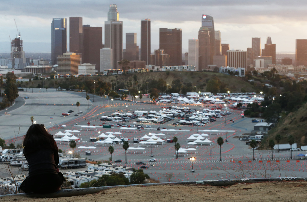 A person sits on a hillside as cars are lined up with people waiting to receive vaccines at a mass COVID-19 vaccination site at Dodger Stadium, with the downtown skyline in the background, on January 22, 2021 in Los Angeles, California.