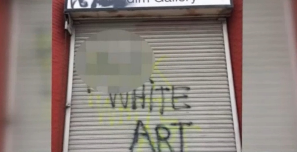 Vandalized garage door of Nicodim Gallery in Boyle Heights, with the words