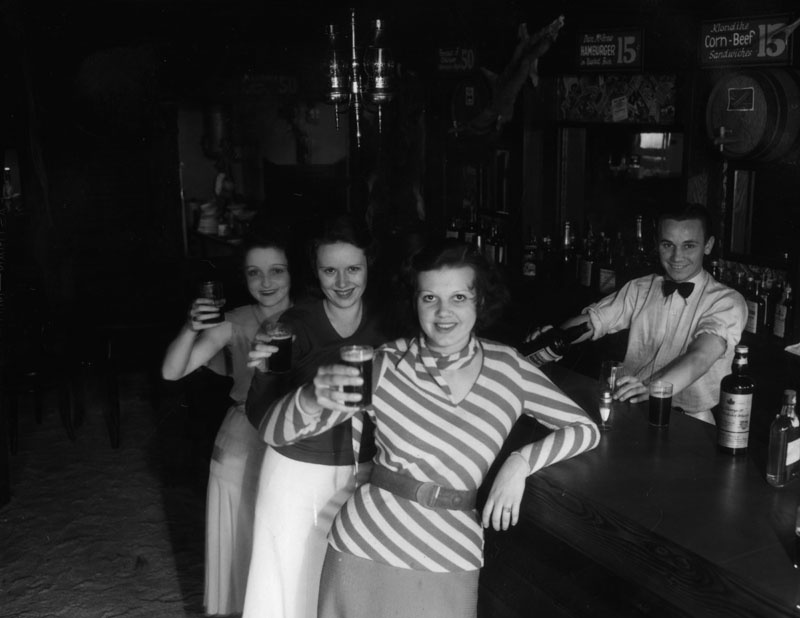 Female patrons at the Malamute Saloon, which was reportedly the first bar to open in Los Angeles after the 1933 repeal of Prohibition. The bar was designed to look like the log cabin Malamute Saloon near Fairbanks, Alaska, made famous in a poem by Robert W. Service. The L.A. version of the saloon featured a log cabin attached to a giant bottle. Circa 1933.