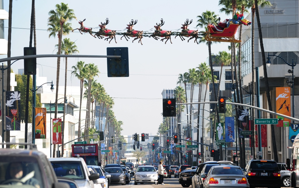Traffic flows along Wilshire Boulevard in Beverly Hills beneath suspended lifesize figures of Santa Claus delivering toys, 2011.
