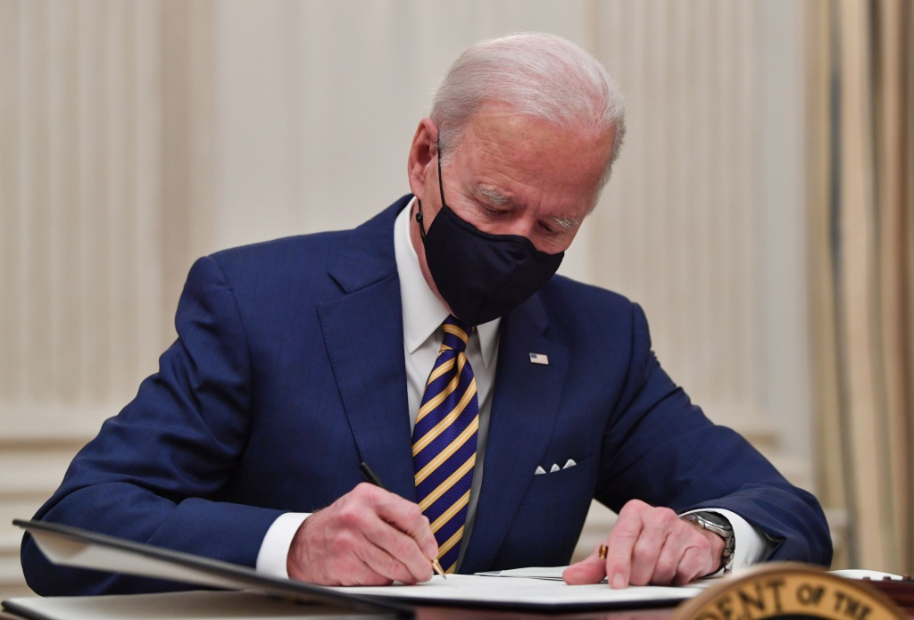 US President Joe Biden signs executive orders for economic relief to Covid-hit families and businesses in the State Dining Room of the White House in Washington, DC, on January 22, 2021.