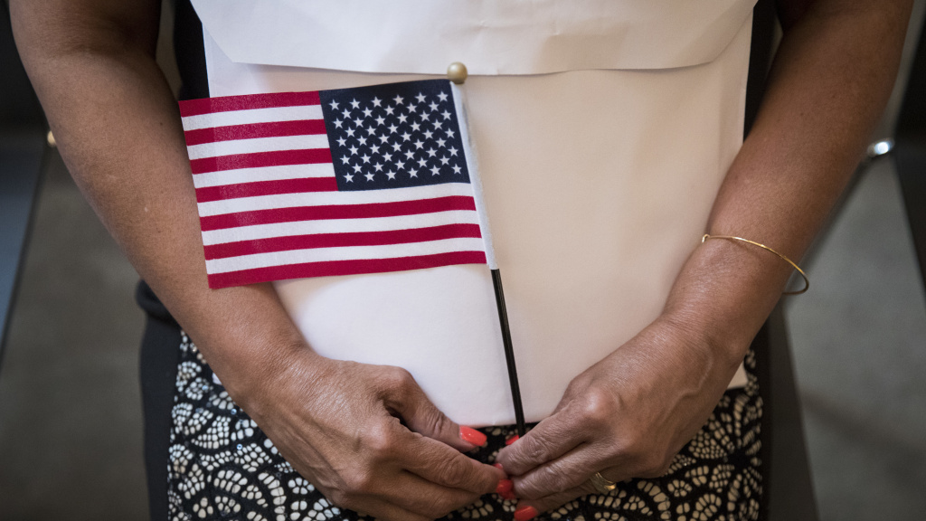 A participant in a 2018 naturalization ceremony holds a U.S. flag in New York City.
