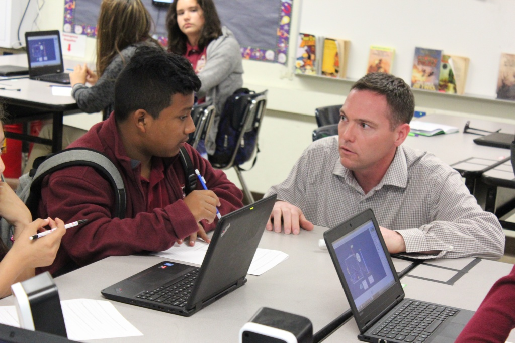 Andrew Osterhaus, a science teacher at Animo Florence-Firestone Middle School, a charter school in South L.A., assists a student as he works on a worksheet.