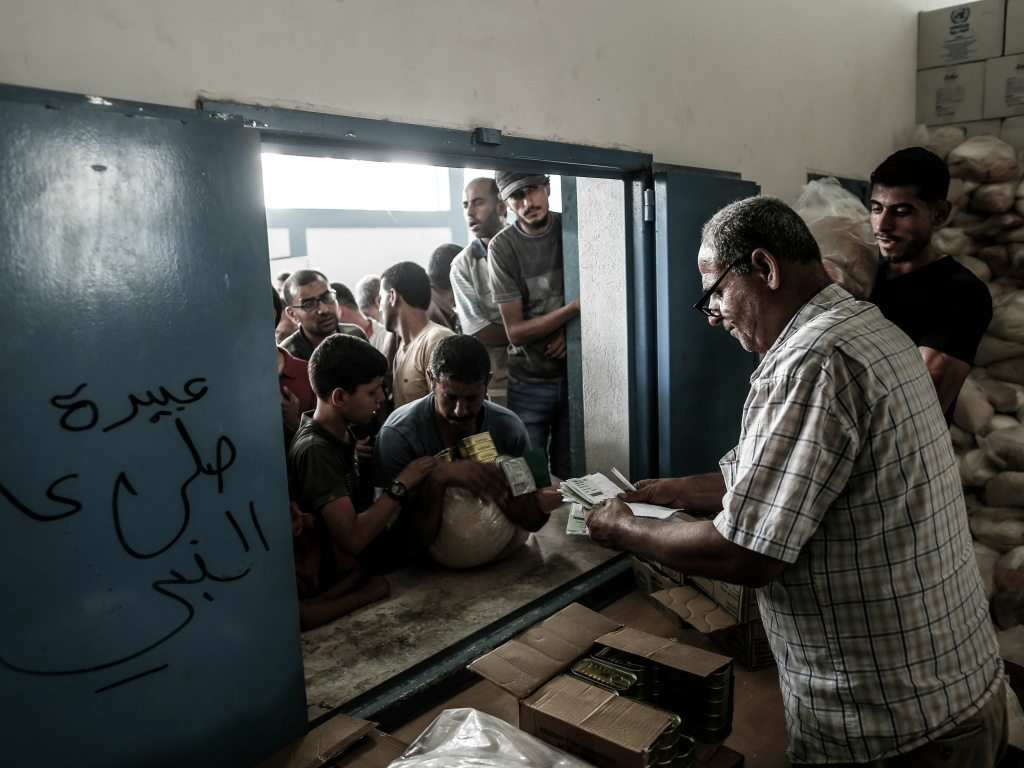 Palestinians receive aid at a United Nations food distribution center in Jabalia refugee camp in the northern Gaza Strip this week.