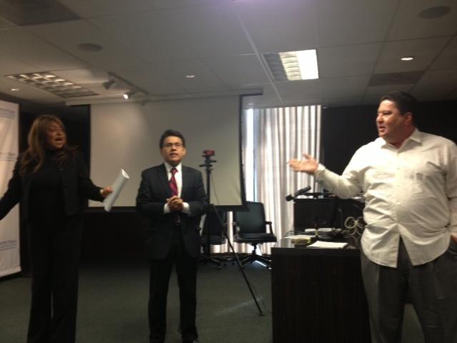 Central Basin Board member Art Chacon (right) confronts board member Leticia Vasquez (left) as Bell city councilman Nestor Valencia (center) looks on.