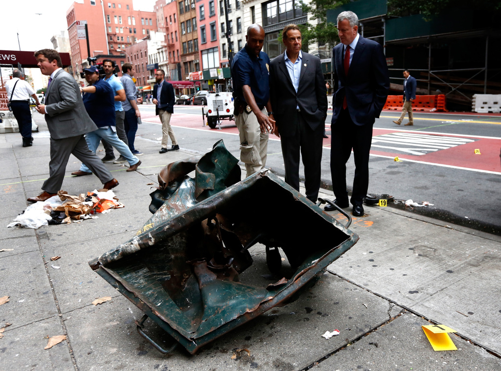 NEW YORK, NY - SEPTEMBER 18: New York Mayor Bill de Blasio (R) and New York Governor Andrew Cuomo (C) stand in front of a mangled dumpster while touring the site of an explosion that occurred on Saturday night on September 18, 2016 in the Chelsea neighborhood of New York City.