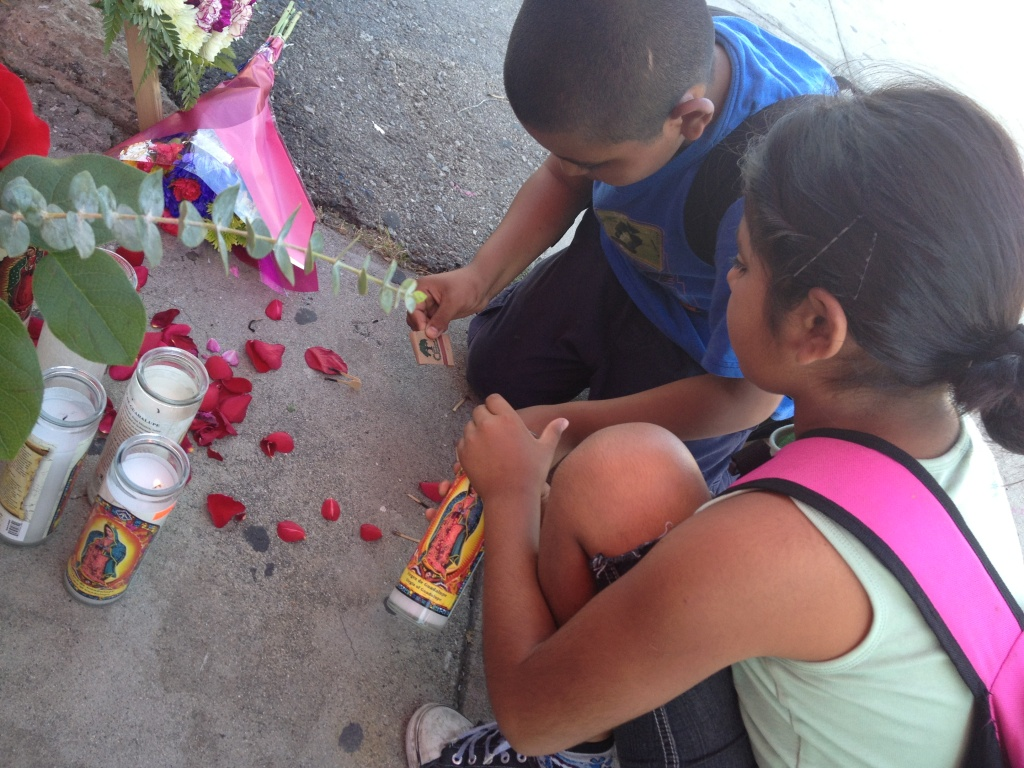 Two children try to light a candle at a memorial for Martha Sanchez, a store clerk who died Tuesday night during a robbery. Many of the parents and children in the area said they knew Sanchez.