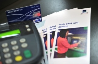 A photo illustration shows a debit card being swiped at a Wachovia Bank.