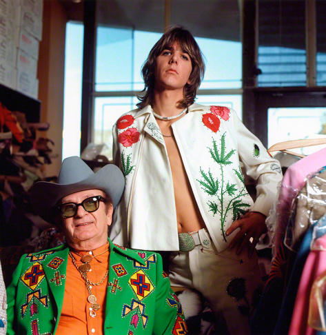 Gram Parsons (standing), adopting the rhinestone look of his country music heroes, in a personalized suit designed by Nashville's favorite tailor, Nudie Cohn (seated), at Nudie's Rodeo Tailors shop, Los Angeles, 1968.