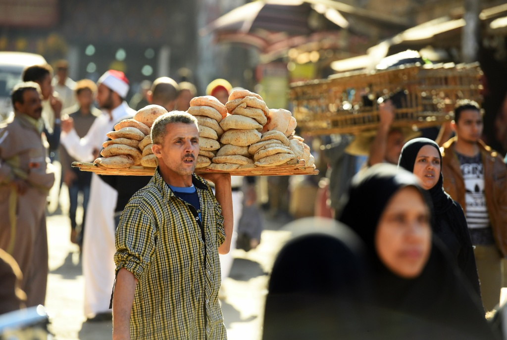 An Egyptian man sells bread outside the al-Azhar mosque in Cairo on December 8, 2017.