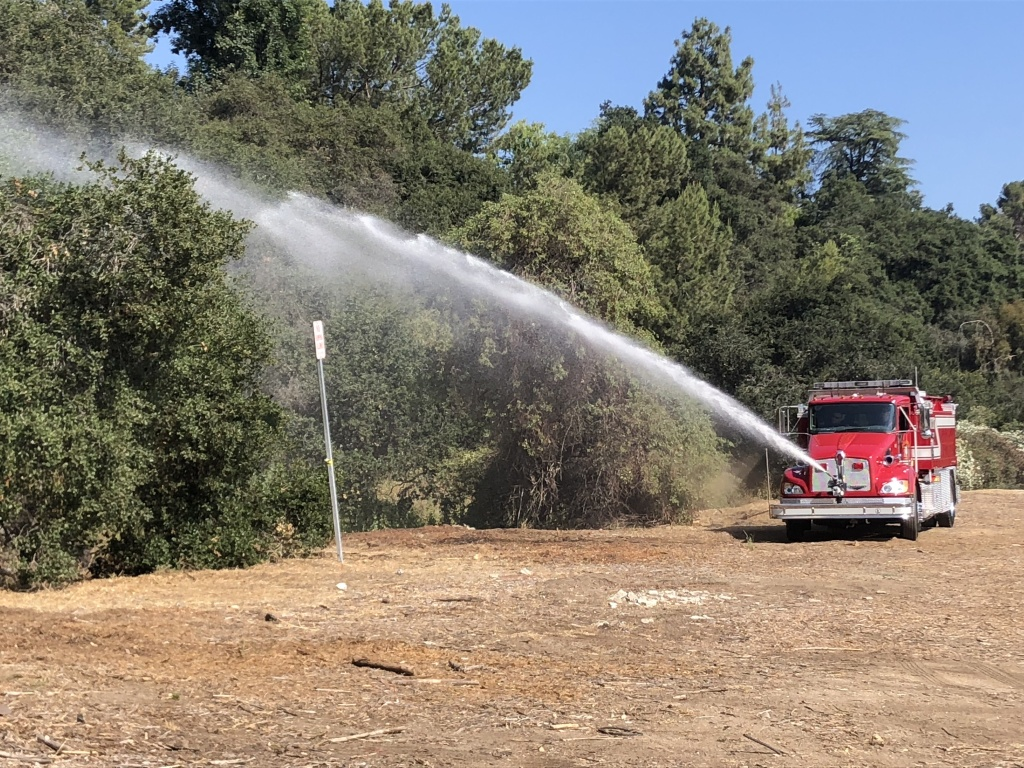 Firefighters spray fire retardant on brush near Rose Bowl to prepare for fireworks.