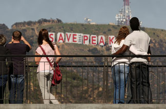 Visitors to the Hollywood and Highland complex view the iconic 450-foot-long Hollywood sign after activists covered it with banners during an effort to prevent the building of houses there on February 13, 2010.