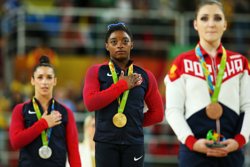 Gold medalist Simone Biles (C) of the United States stands on the podium for the national anthem at the medal ceremony for the Women's Individual All Around on Day 6 of the 2016 Rio Olympics.