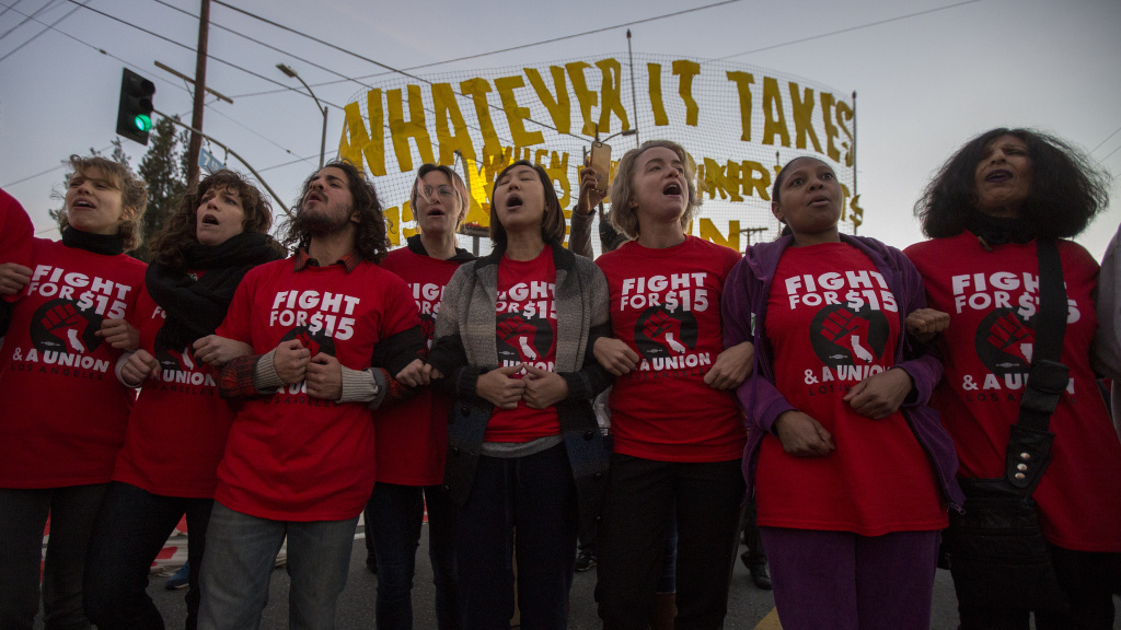 Striking McDonald's restaurant employees lock arms during nationwide