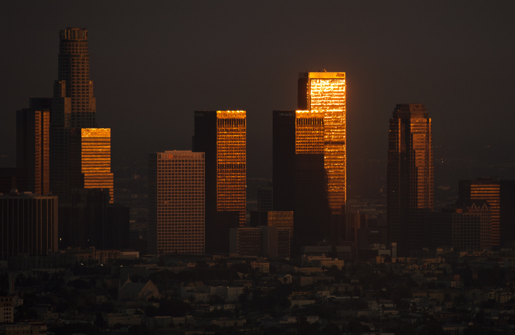 A sun reflects on highrises in downtown during sunset in Los Angeles, California on August 21, 2013.