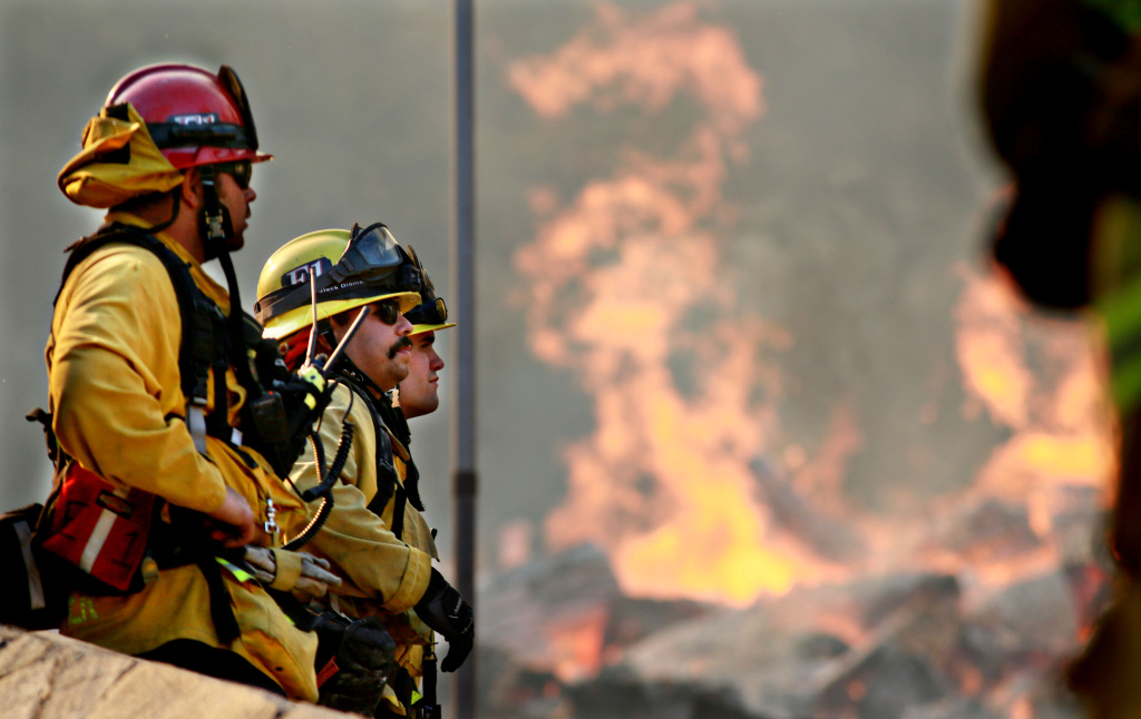 Firefighters battle a blaze at the Salvation Army Camp on November 10, 2018 in Malibu, California. The Woolsey fire has burned over 70,000 acres and has reached the Pacific Coast at Malibu as it continues grow.