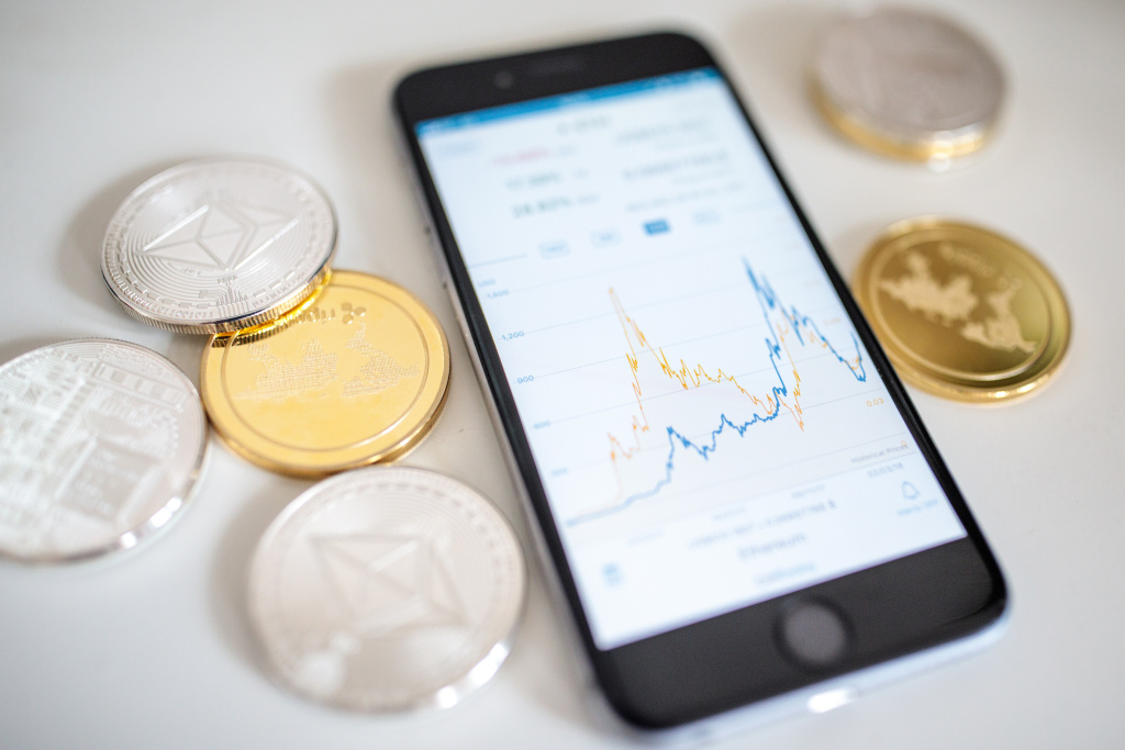 In this photo illustration of the litecoin, ripple and ethereum cryptocurrency 'altcoins' sit arranged for a photograph beside a smartphone displaying the current price chart for ethereum on April 25, 2018 in London, England