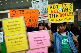 Angel Sequeira holds a sign during a rally against the proposed California budget cuts in front of Gov. Jerry Brown's office on Jan. 10, 2011 in Los Angeles. Several union and community activist groups representing the disabled attended the rally.