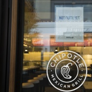 "A sign saying ""we hope to be opening soon"" is pictured outside a new Chipotle Mexican Grill location."
