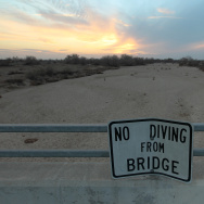 A sign in Bakersfield warns people not to dive from a bridge over the Kern River, which has been dried up by water diversion projects and little rain.