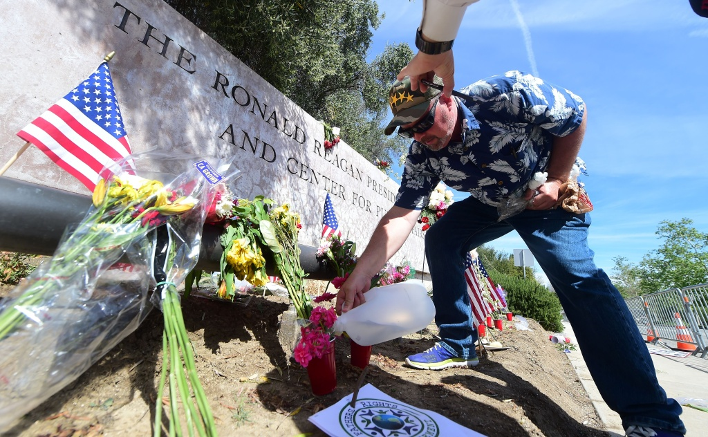 San Luis Obispo resident Dane Senser adds water to flowers at a makesihft memorial for the late Nancy Reagan  outside the Ronald Reagan Presidential Library in Simi Valley, California on March 9, 2016.