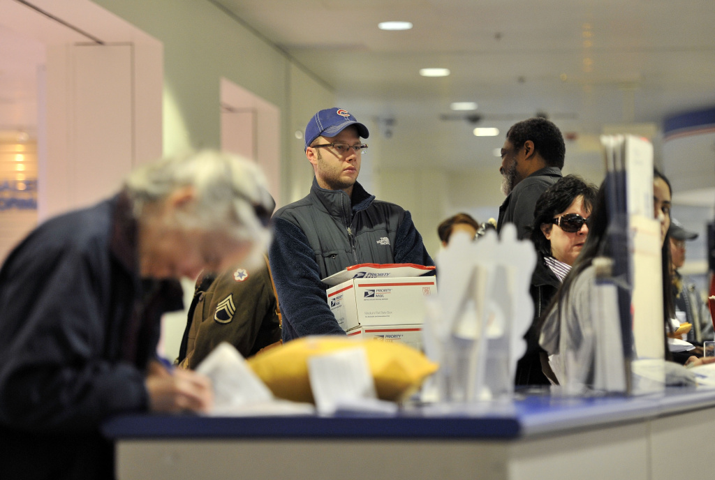 Aaron Pupa (C) waits in line at the customer counter at the Main Post Office on Dec. 19, 2011 in Chicago, Illinois.
