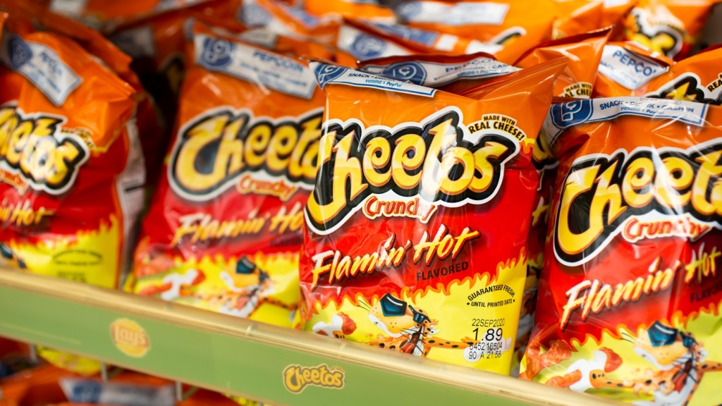 Multiple bags of Flamin' Hot Cheetos on display at a grocery store.