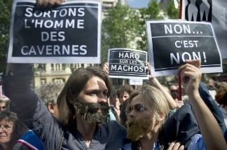 Women, mostly members of feminist groups, hold placards reading 'Let's Get Men Out Of Their Caverns' (L) as they stage a demonstration against the political and media reaction to the sexual assault allegations against former IMF chief Dominique Strauss Kahn in Paris on May 22, 2011.