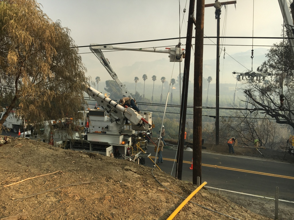 Utility crews work to restore power lines that were burned over on Highway 150 about 3 miles south of Thomas Aquinas College, where the Thomas Fire began.