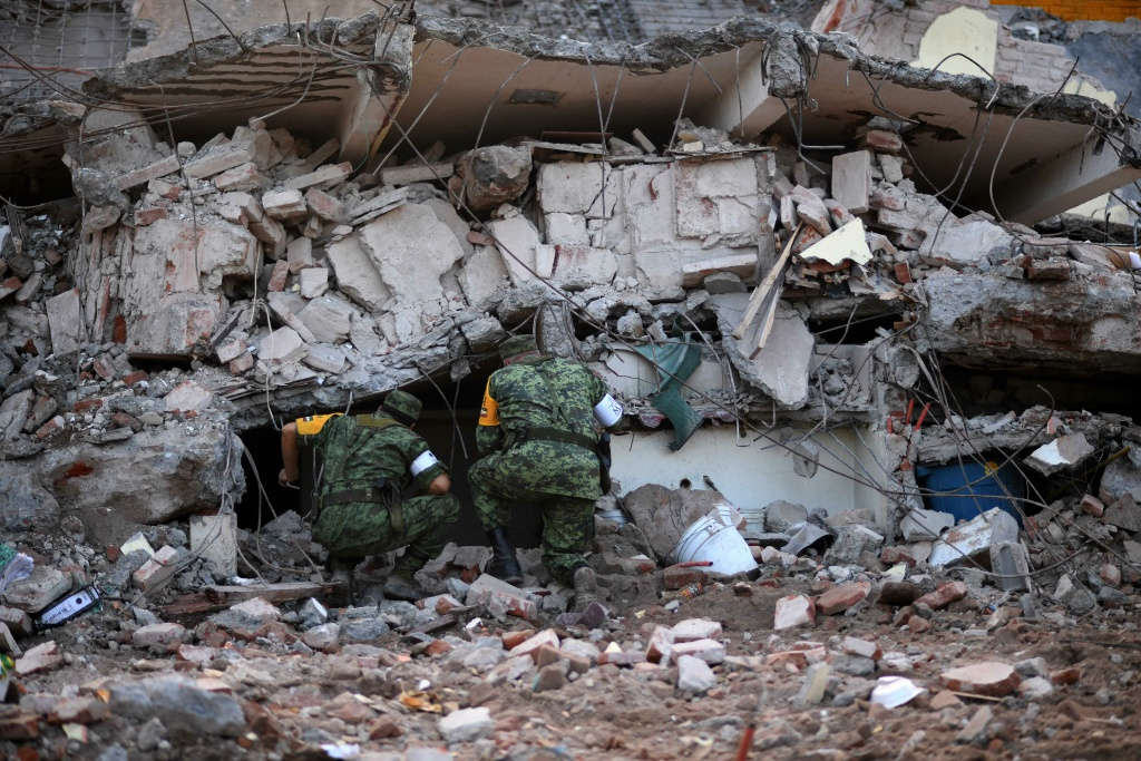 Soldiers with specially trained dogs search for survivors amid the ruins of buildings knocked down by a 8.1-magnitude quake in Juchitan de Zaragoza, Oaxaca on September 7, 2017.