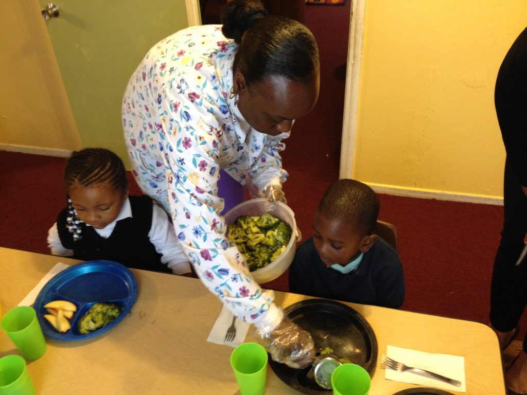 Teacher, Yolanda Carter, serves preschoolers lunch using portion sizes suggested by the USDA.