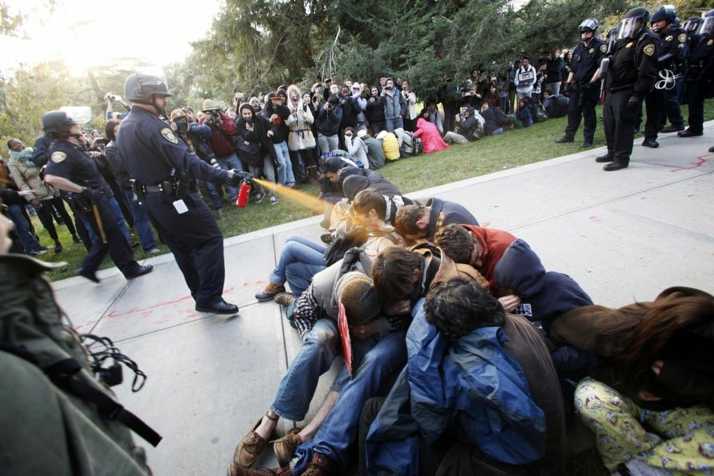 File: In this Nov. 18, 2011 file photo, University of California, Davis Police Lt. John Pike uses pepper spray to move Occupy UC Davis protesters while blocking their exit from the school's quad in Davis, Calif.