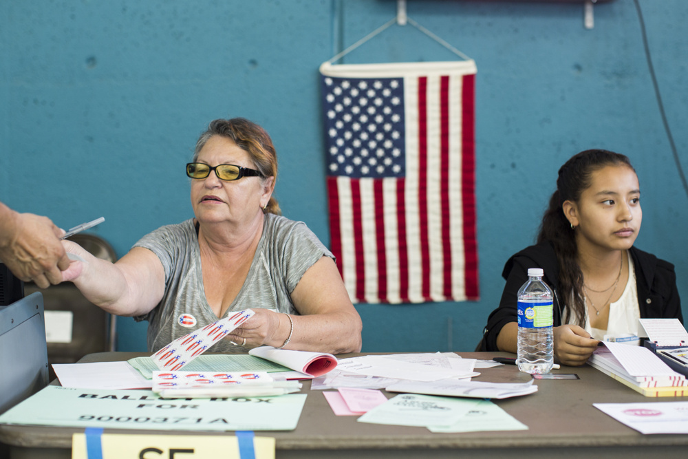 Poll workers Apolonia Corrales, left, and Laura Pallares help voters cast their ballots at Echo Park Deep Pool in Los Angeles on Tuesday afternoon, Nov. 8, 2016. Pallares is a student at Edward R. Roybal Learning Center and this was her first time volunteering.