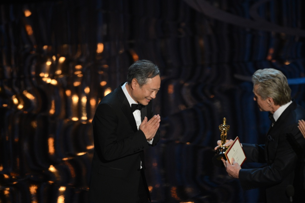 Director Ang Lee accepts the Oscar for Best direting from actor Michael Douglas onstage at the 85th Annual Academy Awards on February 24, 2013 in Hollywood, California.