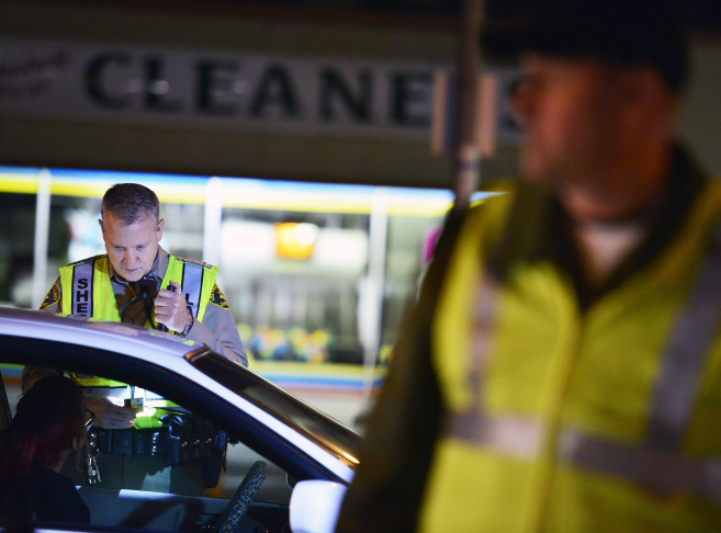 Deputy Fertal of the Los Angeles County Sheriff's Department, left, checks a motorist's dirver's license at a DUI checkpoint in Bellflower on March 6, 2014.
