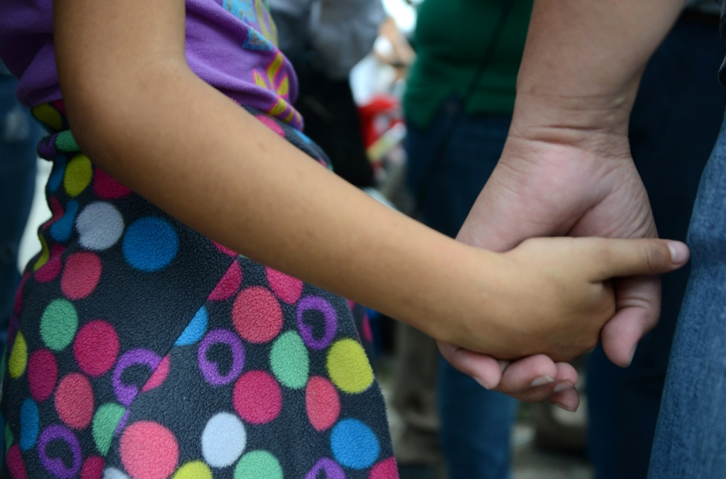 FILE PHOTO: A Honduran child holds a parent's hand after being reunited with her family. Parents who sent for their children to come to the U.S. via smugglers could face prosecution and deportation under a new Trump administration immigration directive.