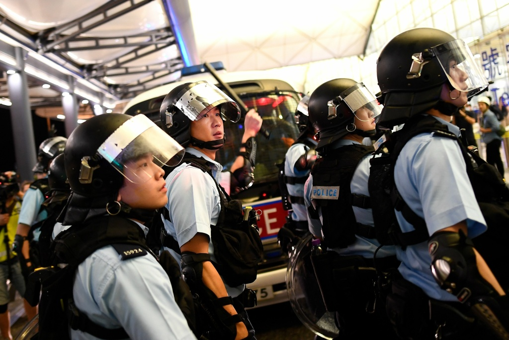Police secure Terminal 1 after a scuffle with pre-democracy protestors at Hong Kong's International Airport on August 13, 2019