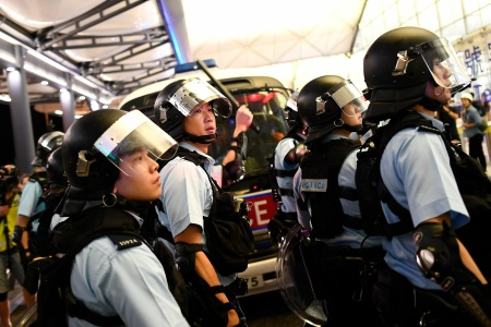 Police secure Terminal 1 after a scuffle with pre-democracy protestors at Hong Kong's International Airport on August 13, 2019.
