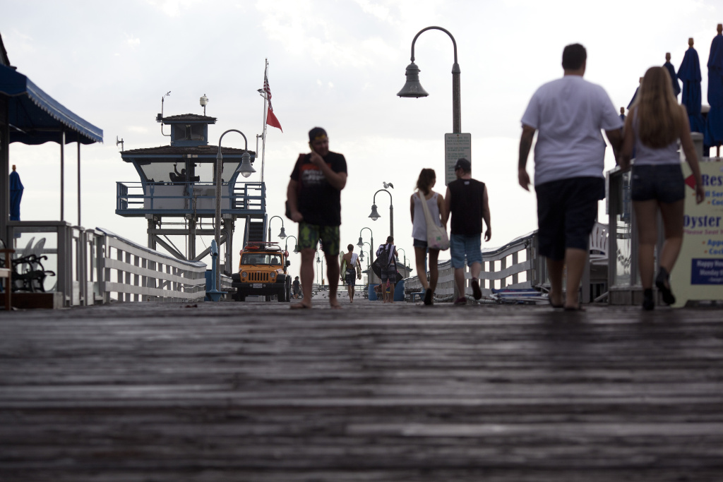 Beachgoers walk along the San Clemente Pier after a storm brought rain  to Orange County Tuesday afternoon. Republicans are battling for the Orange County stronghold.
