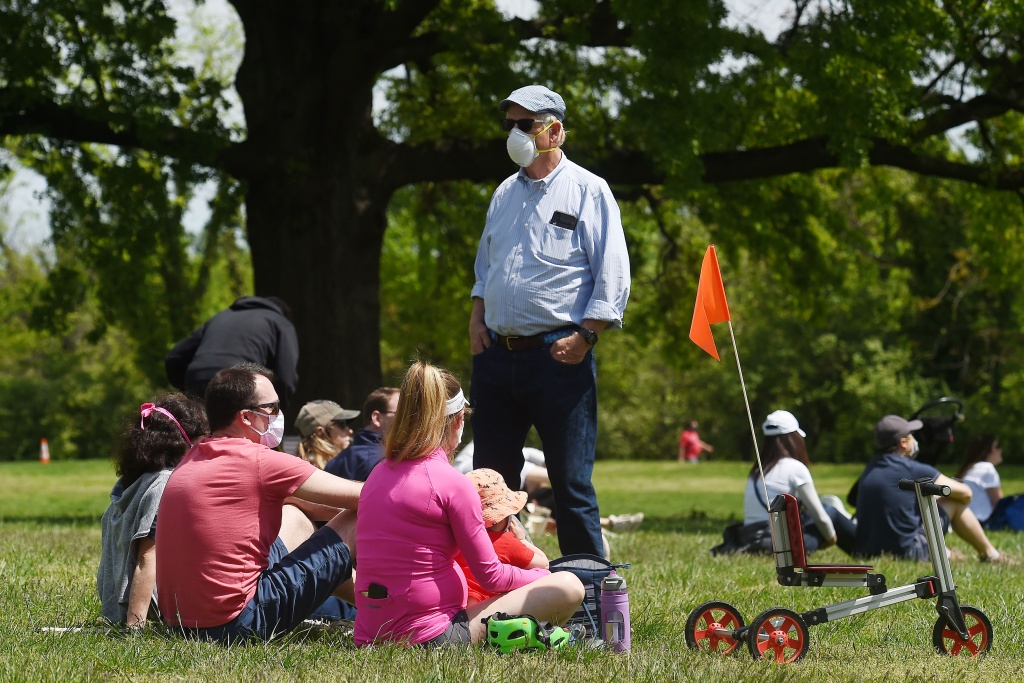 People wearing face masks gather in a park  to watch the US Navy Blue Angels and US Air Force Thunderbirds fly over the Washington, DC, area on May 2, 2020.
