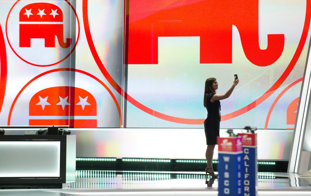 A woman takes a selfie from the stage as preparations get underway for the Republican National Convention at the Quicken Loans Arena in Cleveland, Ohio on July 17, 2016. An estimated 50,000 people are expected in Cleveland, including hundreds of protesters and members of the media.