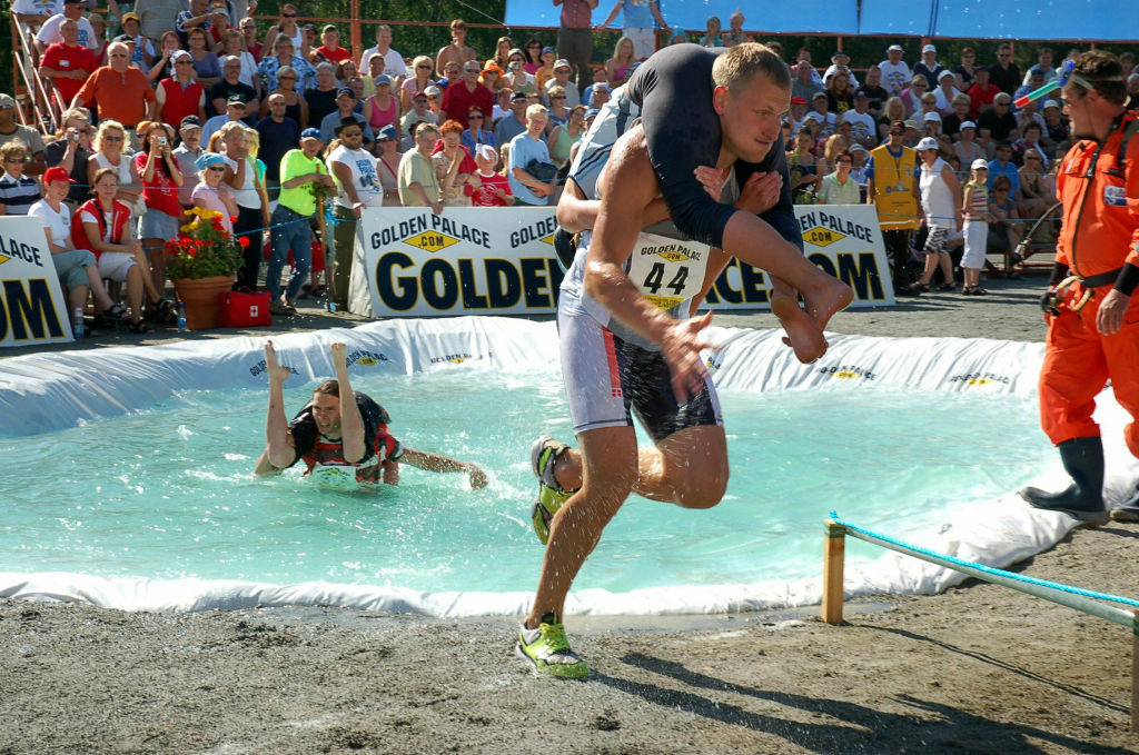 Sonkajarvi, FINLAND: Margo Uusorj carries Sandra Kullas of Estonia 01 July 2006 to win the 2006 wife-carrying world championships in Sonkajarvi, central Finland.