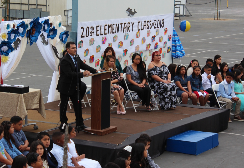 Mario Garcielita (at podium), principal of 20th Street Elementary School just south of downtown Los Angeles, leads a fifth grade graduation — or