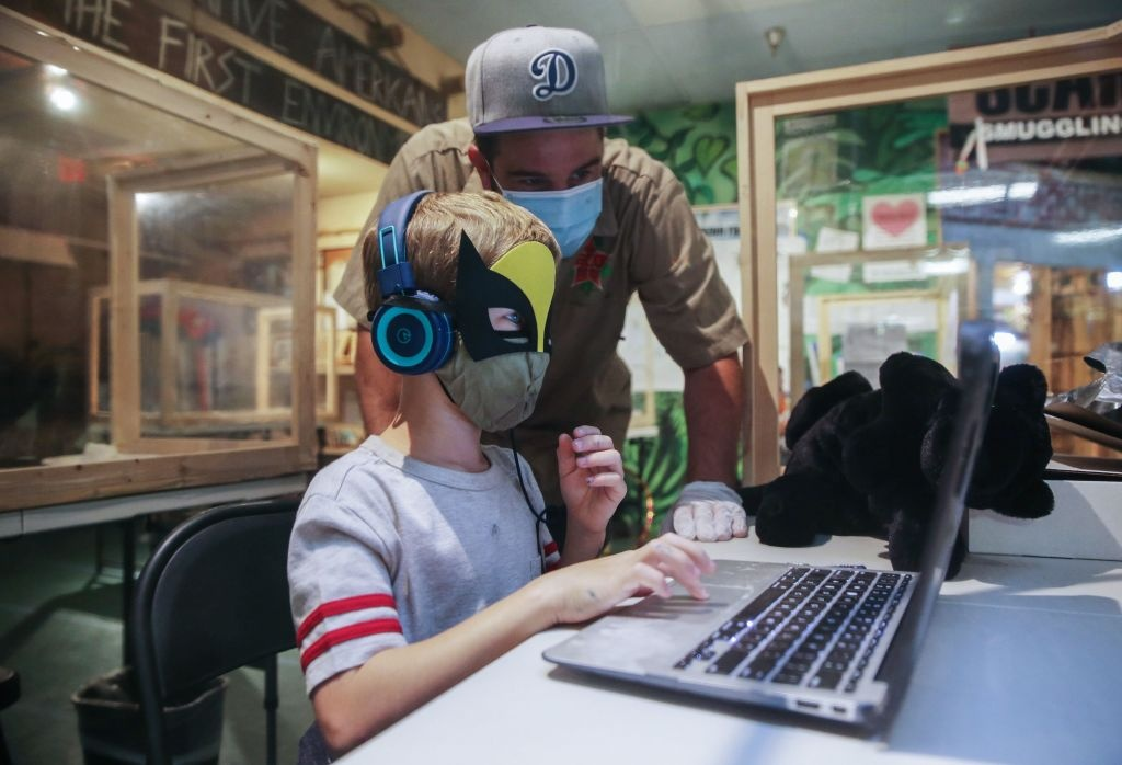 Danny Osborne, Wildlife Director for Eco Station, helps a student seated in a socially distanced protective learning pod during a livestream class at STAR Eco Station Tutoring & Enrichment Center on September 2, 2020 in Culver City, California.