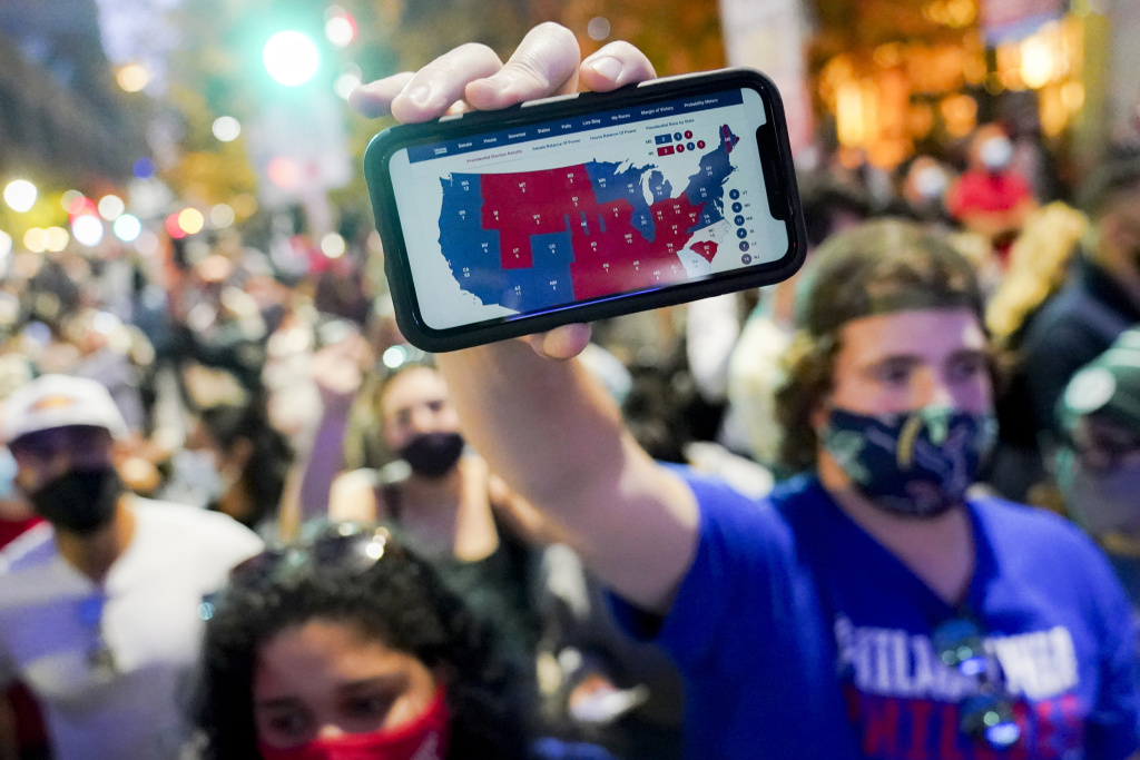 A Joe Biden supporter holds up a phone displaying the Electoral College map in Philadelphia on Nov. 7.