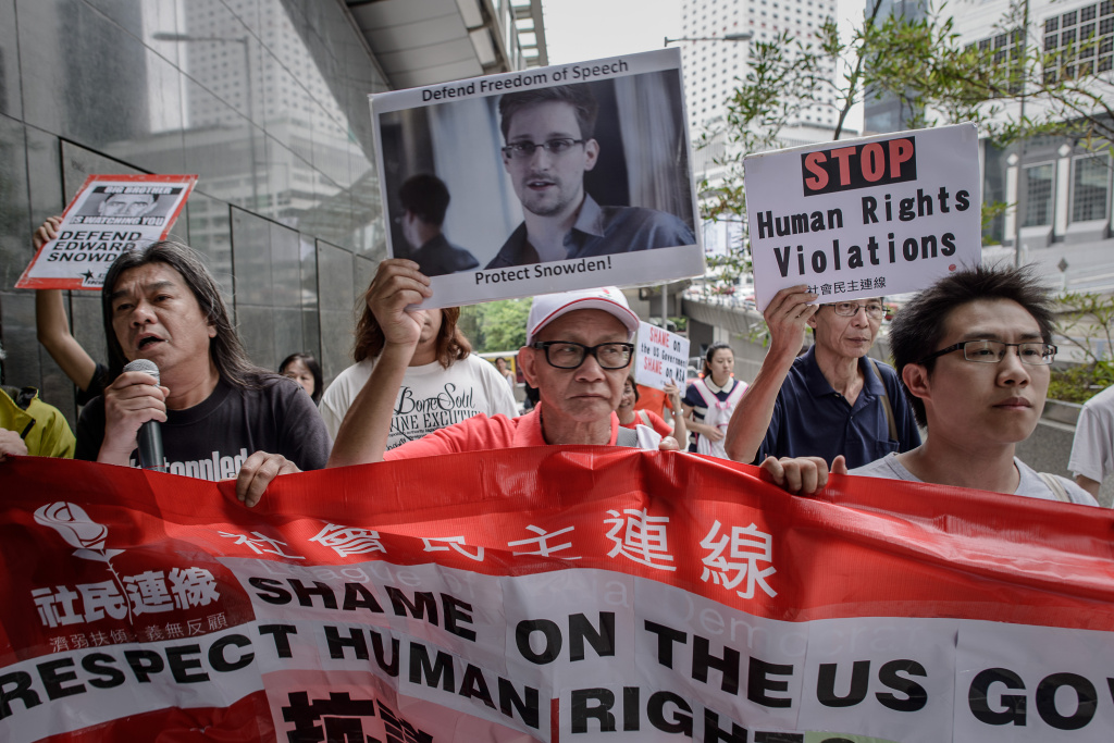 Protesters shout slogans in support of former US spy Edward Snowden as march to the US consulate in Hong Kong on June 13, 2013. Snowden broke his silence on June 12, vowing to fight any bid to extradite him from Hong Kong and accusing Washington's cyber-troops of prying into hundreds of thousands of targets globally including many in China.