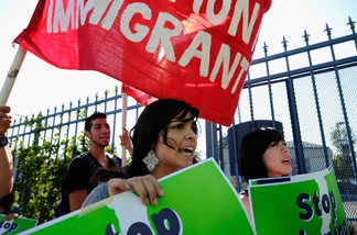 Protesters with Coalition for Humane Immigrant Rights of Los Angeles (CHIRLA) hold signs as they march during an anti Secure Communities program demonstration on August 15, 2011 in Los Angeles.
