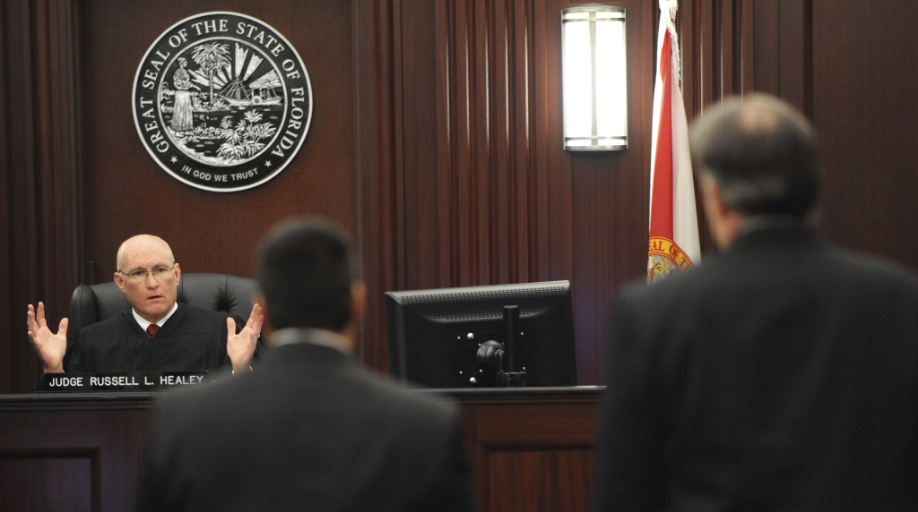 Judge Russell Healey, left rear, explains his answers to three related jury questions to defense attorney Cory Strolla, center, and defendant Michael Dunn, right, before bringing the jury into the courtroom, Saturday, Feb. 15, 2014 in Jacksonville, Fla