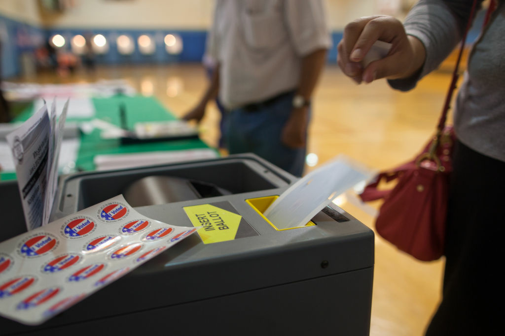 A woman submits her ballot at Estrada Court Community Center in Boyle Heights.