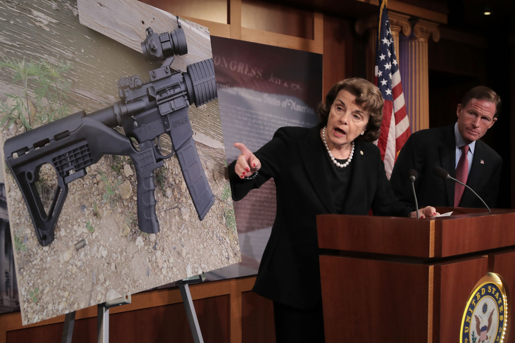 Sen. Dianne Feinstein (D-CA) (C) and Sen. Richard Blumenthal (D-CT) points to a photograph of a rifle with a
